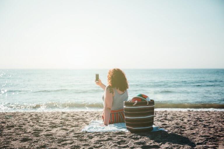 young woman takes selfie while sitting on sunny beach 在Instagram或Facebook中是否常看見很多漂亮又帥氣的自拍照呢? 不論是透過相機或是智慧型手機拍攝,在自拍畫面中的技巧大家都掌握多少呢? 不要小看這些技巧,學會自拍對於商業攝影也是一大幫助喔! 透過自拍秘訣的了解,會更懂得在活動直播中展現自己,更懂得抓自己臉好看的角度。 現在不只是女孩愛自拍,連男孩也更想懂得展現自己帥氣的一面, 在本文中,總結了些自拍中的關鍵,介紹給初級自拍者。